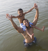 Son sitting on father's shoulders in a lake